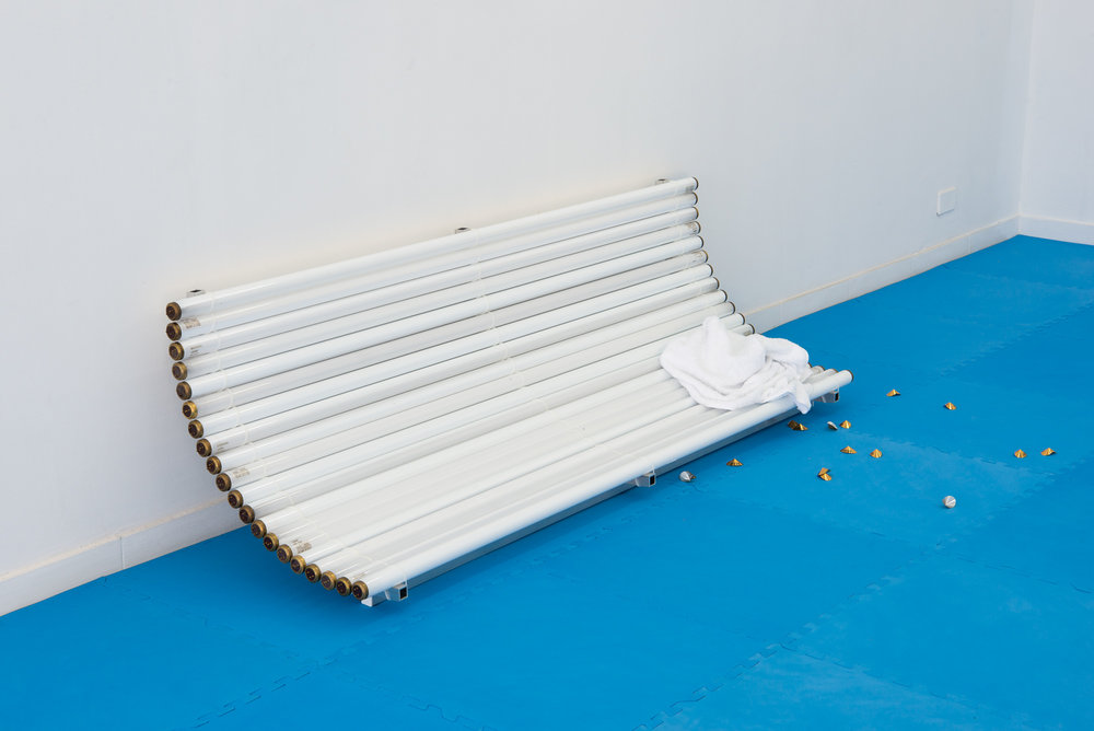 Golden Brown Texture Like Sun, 2017  Used sun tanning bulbs, aluminium, eye-protectors, towel 53 x 178 x 56 cm ---
