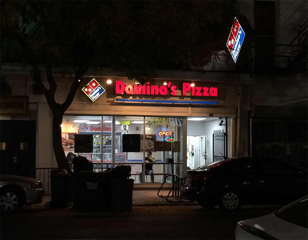 A performer sits in the window of Domino's storefront