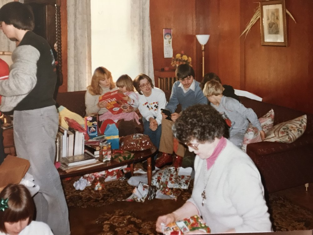 Christmas at Grandma's. Grandma opening a present in the foreground. I'm with my mom in the background, sporting a Strawberry Shortcake dress and admiring my new See N Say.
