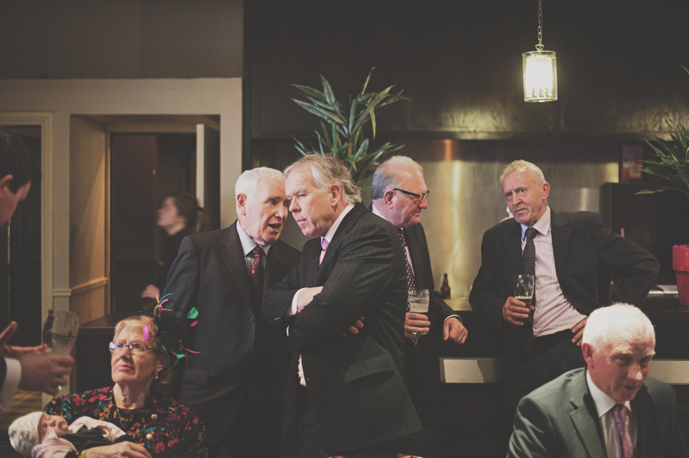 men chatting at wedding