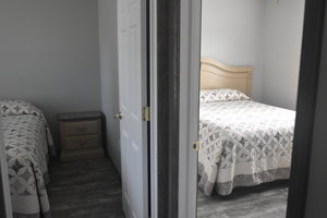 Lucky Horseshoe Cottage #17 - Interior 1st Bedroom with Queen Bed and Mirror.JPG