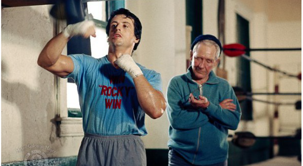 """Rocky"" (1976)   Rocky Balboa, a small-time boxer gets a supremely rare chance to fight the heavy-weight champion, Apollo Creed.   Sylvester Stallone wore this ""Win Rocky Win"" t-shirt while training hard for the fight."