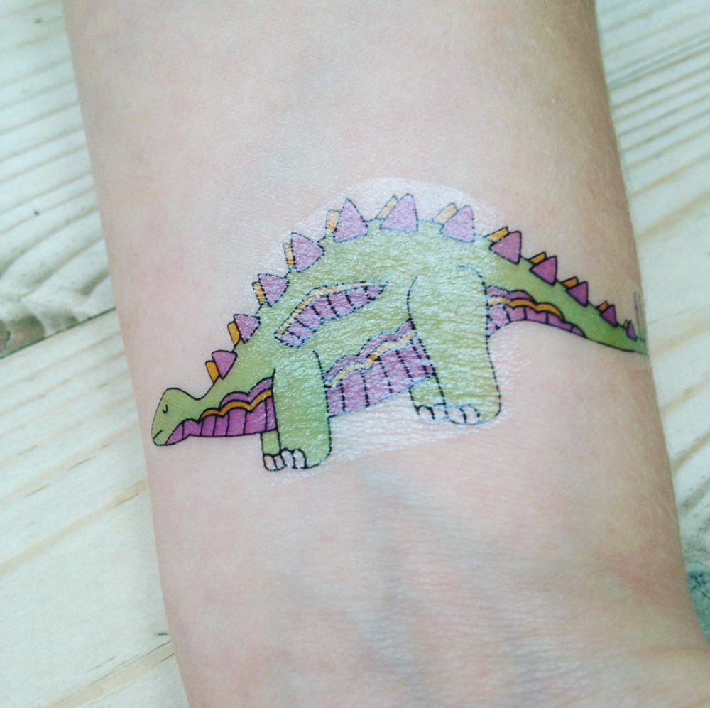 Green dinosaur transfer tattoo on  a wrist