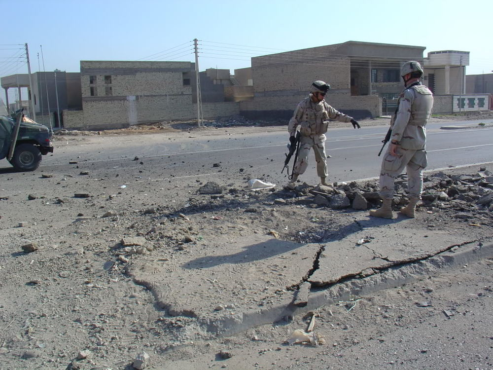 Soldiers evaluate a roadside bomb detonation, May, 2005.