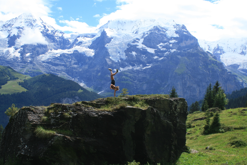 Ruby with her signature one arm handstand in one of the most impressive trough valleys in the Alps, Lauterbrunnen, Switzerland