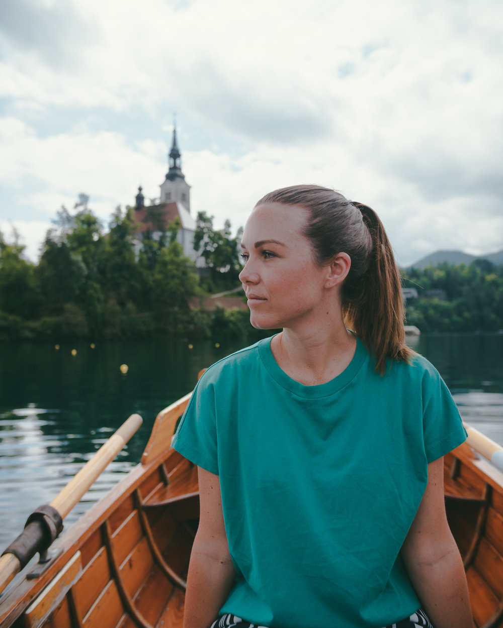 Phoebe taking in the views at Lake Bled, Slovenia, while rowing a wooden boat with her friend Boyan (Boyanoo)