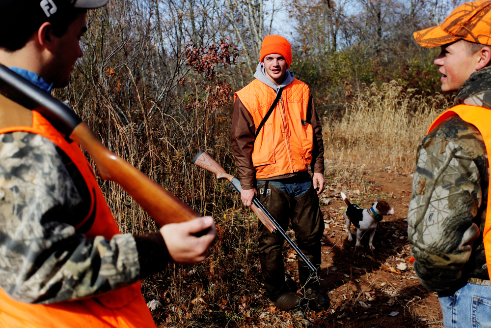 Koons chats with his friends Reed Morgan, left, and Bryce Smathers, right, while rabbit hunting outside of Millfield, Ohio.