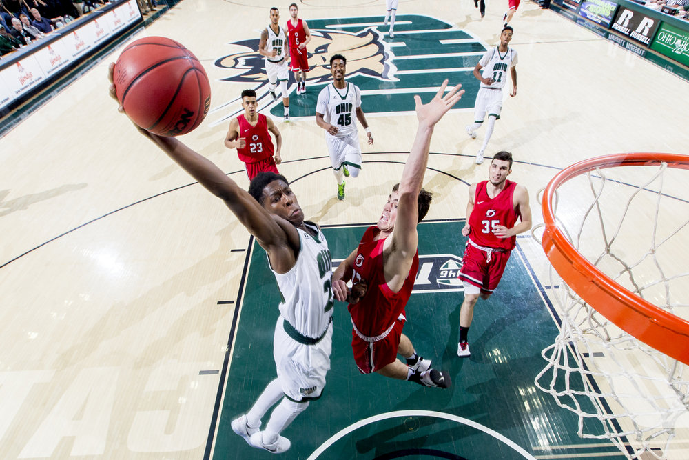 Ohio Bobcats Rodney Culver (23) goes for a dunk past Rio Grande's Kaileb Sheets (12) at the Convocation Center in Athens, Ohio.