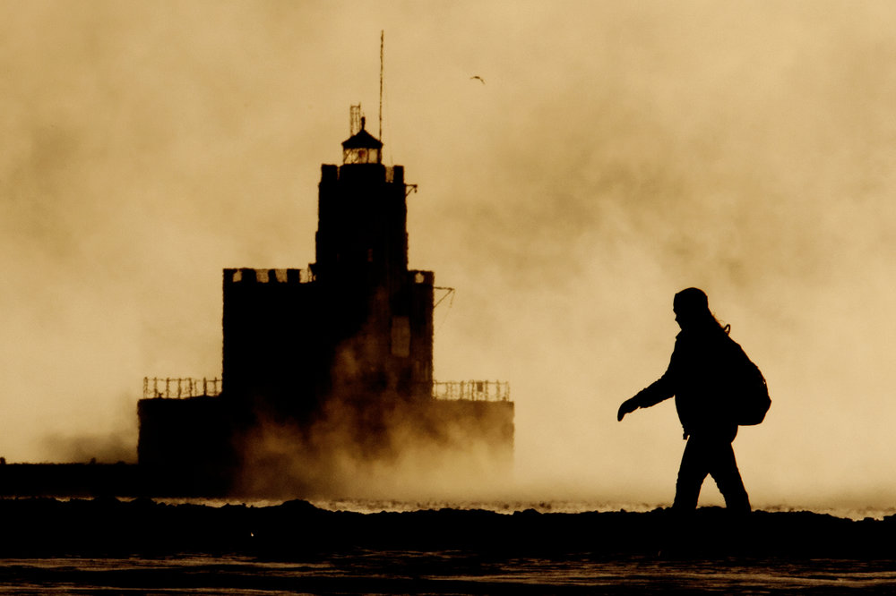 A person braves sub-zero temperatures and a -15°F windchill while walking through Lakeshore State Park in downtown Milwaukee, Wisconsin.