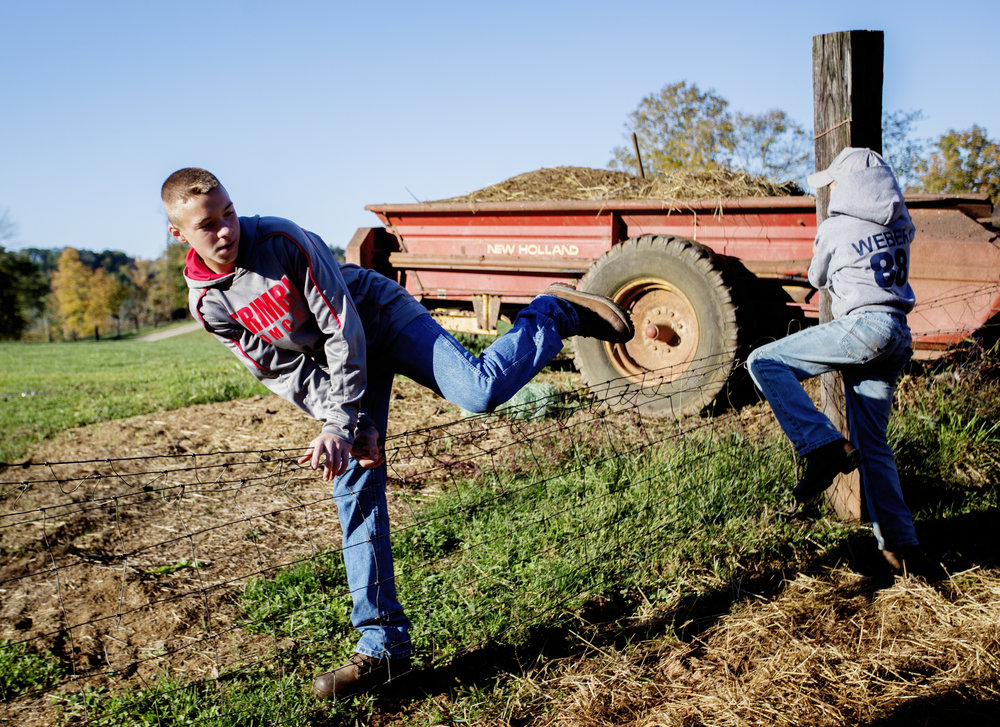 Braden and Levi Weber climb over a fence in their farm yard.