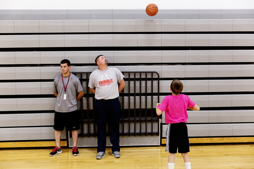 Reitano observes basketball practice as Steve Weber looks at Levi Weber's ball in the air.