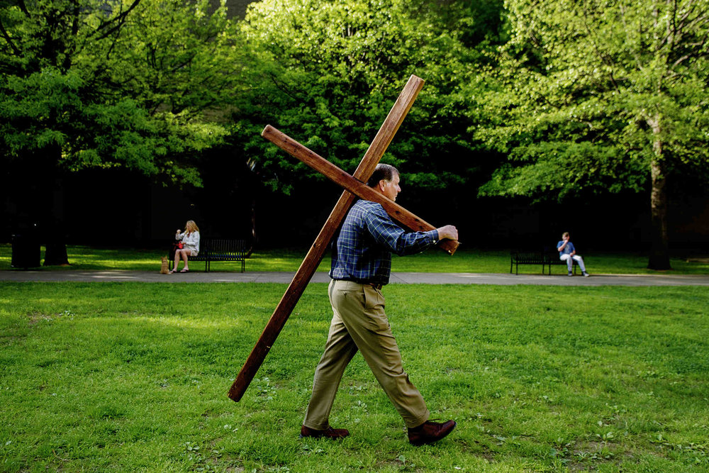Bill Bullock, of Knoxville, carries the cross through Krutch Park during a Stations of the Cross event held by Downtown Ministry Cooperative in downtown Knoxville.