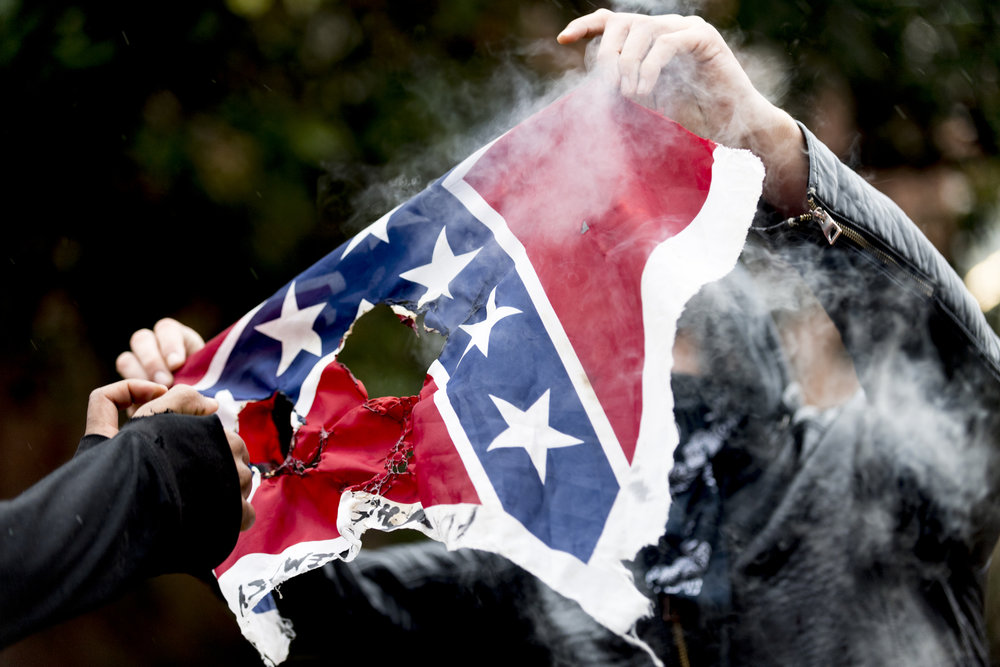 A protestor defaces a Confederate battle flag during a protest against a visit to University of Tennessee by Traditionalist Working Party leader Matthew Heimbach on February 17, 2018.