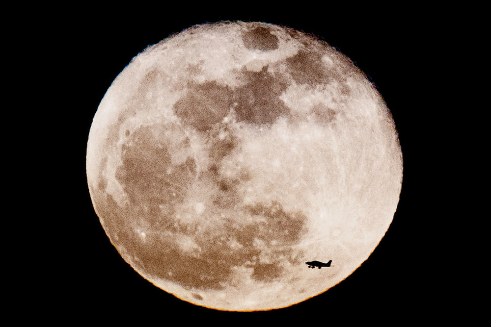 A plane leaving Island Home Airport flies in front of a supermoon as it rises above Knoxville, Tennessee on Tuesday, January 2, 2018. The January supermoon, also known as the Wolf Moon, orbits some 221,559 miles from Earth.