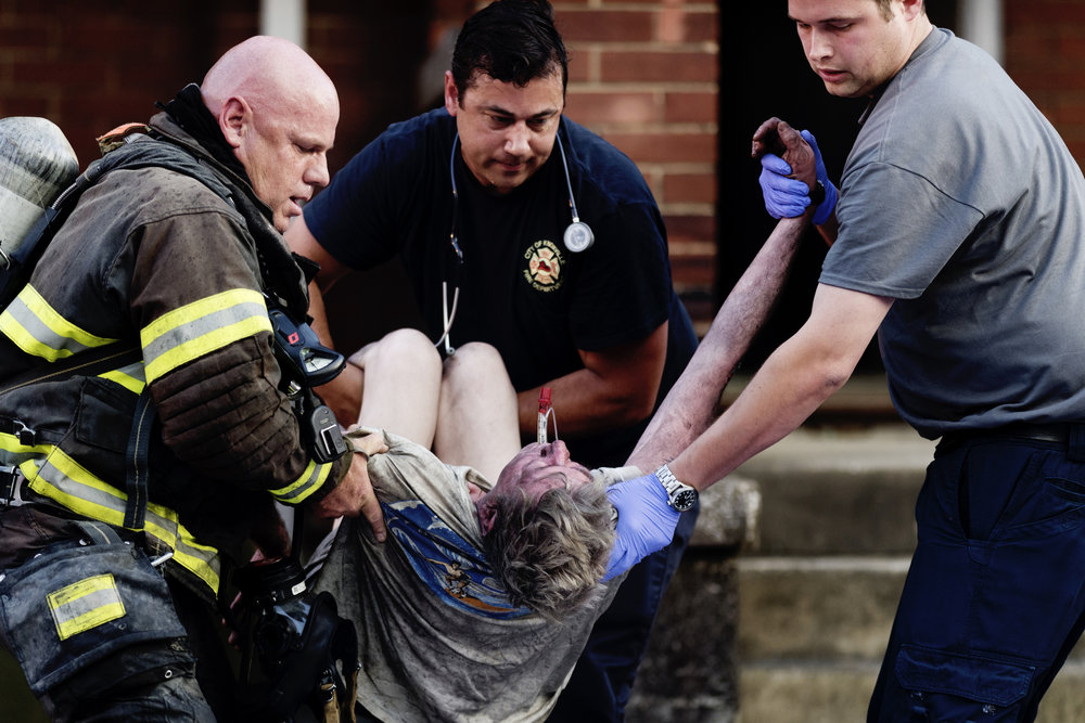 First responders pull a man from a burning building on 1210 Clinch Avenue in Fort Sanders in Knoxville, Tennessee on Saturday, May 19, 2018. KFD rescued a single occupant from the building.