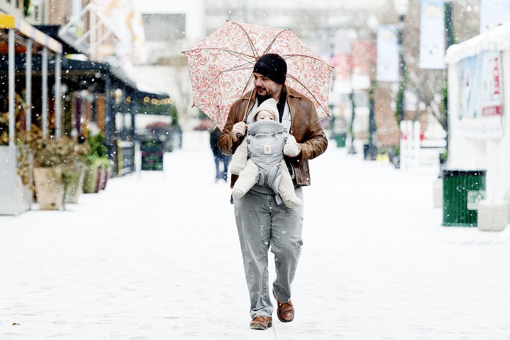 John Texada walks through Market Square with his son Collin, who is 5 1/2 months old, during a brief snowfall in downtown Knoxville, Tennessee on Thursday, January 4, 2018. Texada took his son for a walk so he could experience his first snowfall.