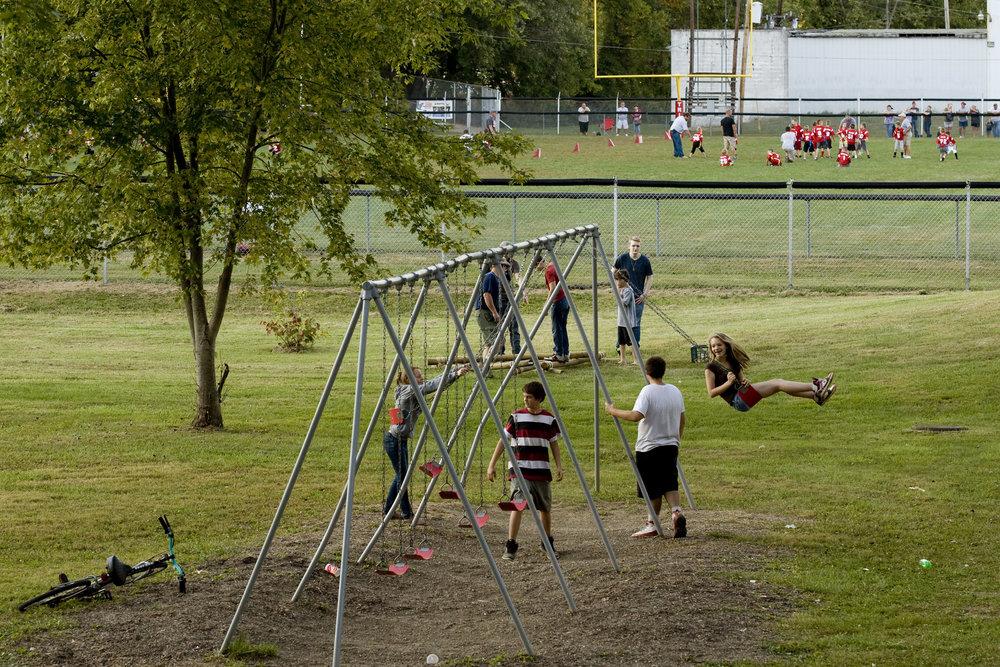 Children play on a swing set at Glouster Memorial Park next to Glouster Stadium in Glouster, Ohio, September 2014.