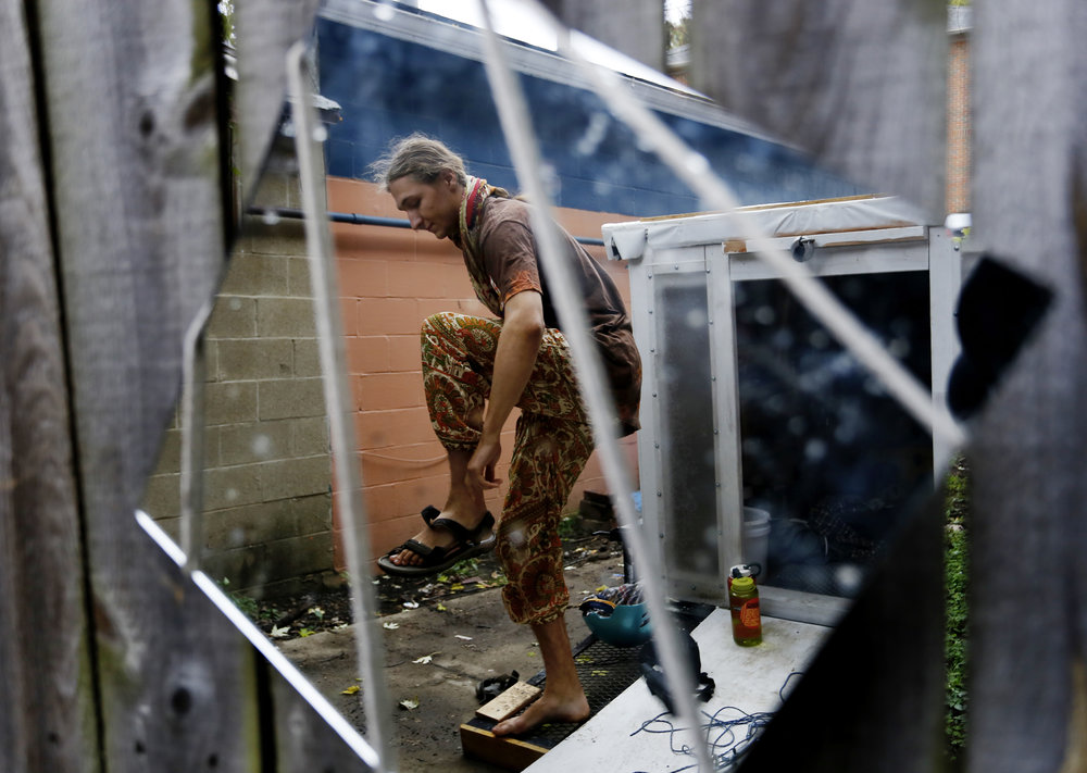 "Nigel Wilson gets dressed in an alley beside his self-built four-wheeled home in Athens, Ohio in 2015. Wilson has chosen to live ""a life of luxury"" free of electricity, internet and other modern conveniences, including living in a home."