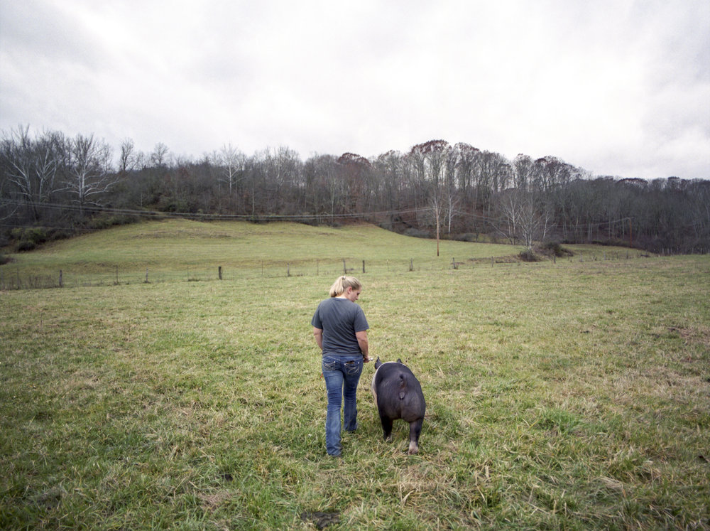 Emily Bush walks with one of her pigs on her farm in Athens County, Ohio. Stereotypes about women in farming still abound within the agricultural community, and Bush works to break those stereotypes by working hard and proving herself.