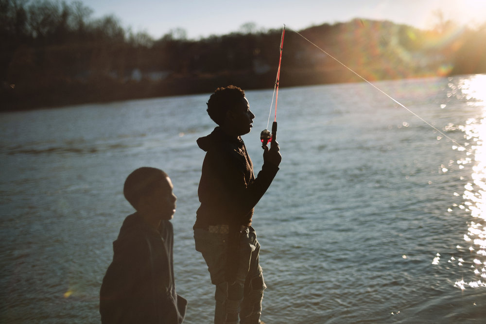"""oKyriek George and his cousin Vákarus Bomar, 8, fish from the Riverside Landing boat dock in Knoxville. After weeks of unusually warm weather, the boys took advantage of the final day of warmth to catch """"anything that bites."""""""