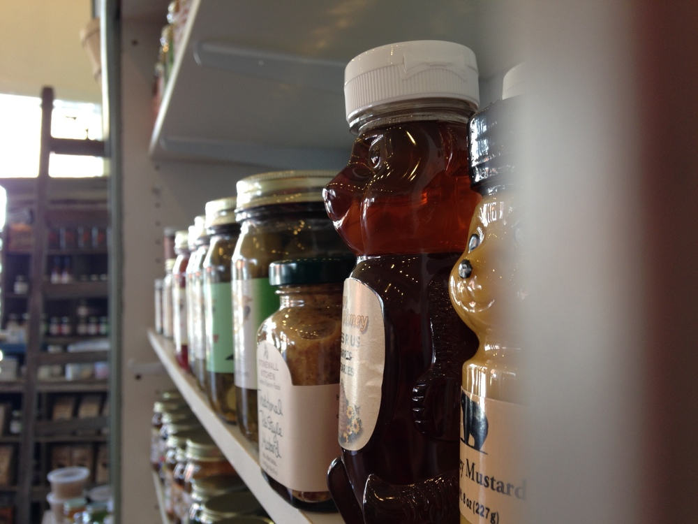 Local honey, condiments and preserves line the rustic wood shelves.