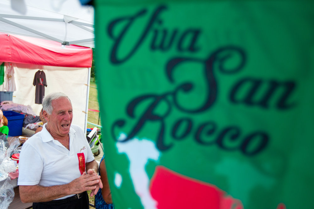 Henry Bufalini talks to friends at the 91st San Rocco Festa in Aliquippa on Friday afternoon. The festival took place over three days and featured live music, vendors, fireworks, a mass and the traditional Baby Doll Dance on Sunday evening.