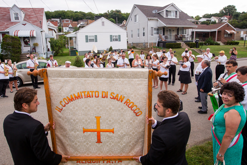 Mario Masantonio, left and his brother Michael hold the San Rocco banner, while the San Rocco Festa Band plays traditional Italian music before going to St. Titus Church in Aliquippa on Sunday morning. The festival, which originated in the town of Patrica, Italy, has been occurring in Aliquippa for 91 years.