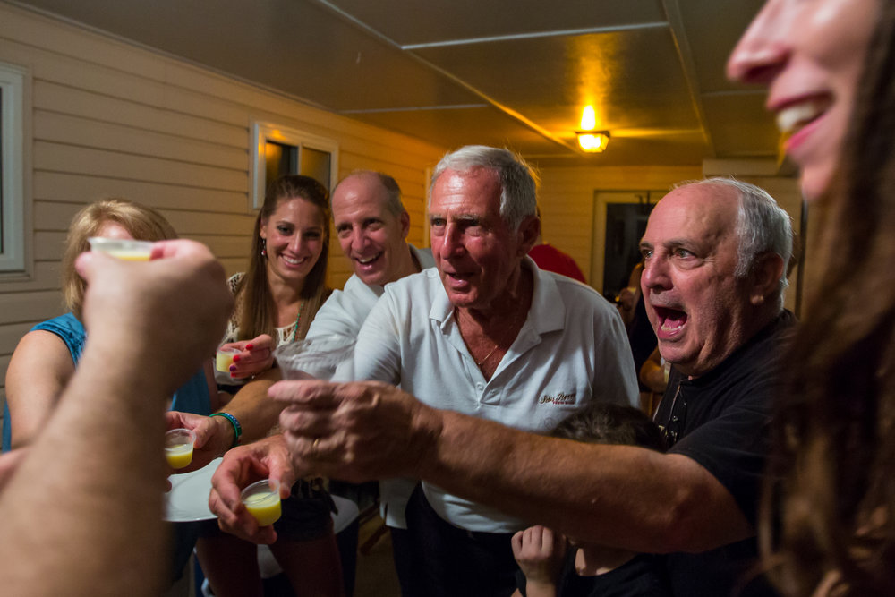 Henry Bufalini, center, raises a shot of limoncello at a close friends house after the first night of the 91st San Rocco Festa in Aliquippa on Friday. Each year after the first night of the festival, family and close friends go to multiple houses to eat and drink.