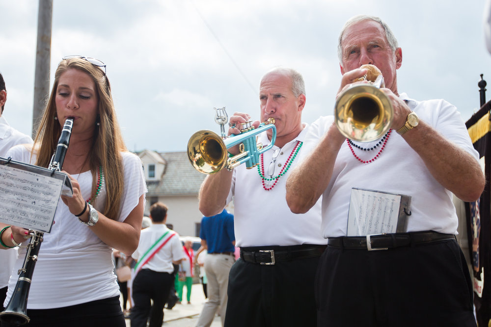 Henry Bufalini, right, his son David, center and his daughter Natalee play with the San Rocco Festa Band during the procession through the streets of Aliquippa on Sunday morning. Henry, David and Natalee are the only three generation family members currently playing in the San Rocco Festa Band.