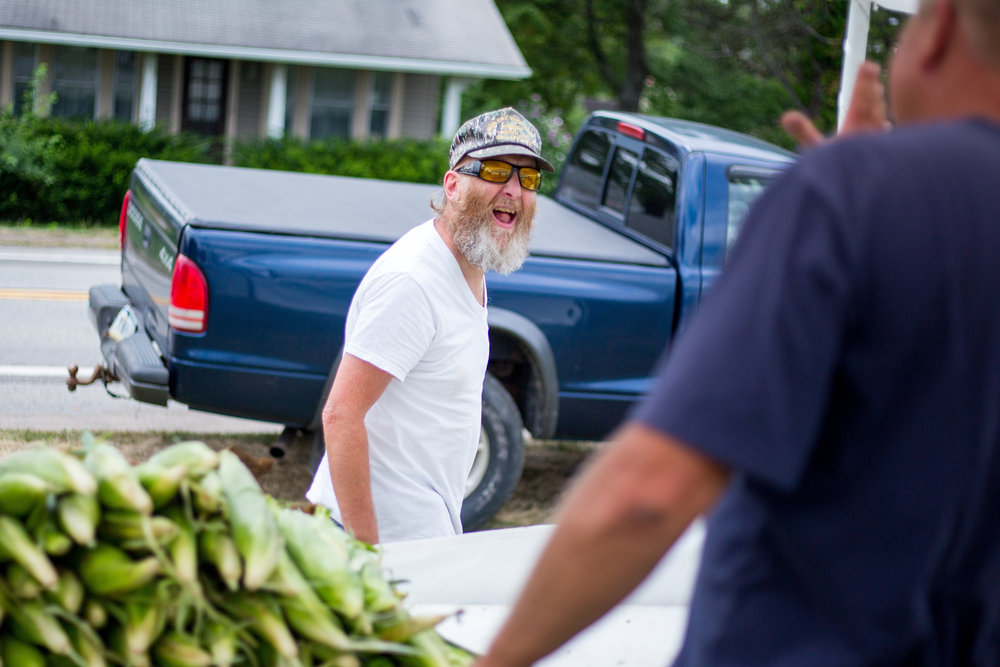 Doug Aiken, left, laughs after getting corn from Mike Wise at his produce stand on Highway 65 in North Sewickley on Tuesday afternoon.