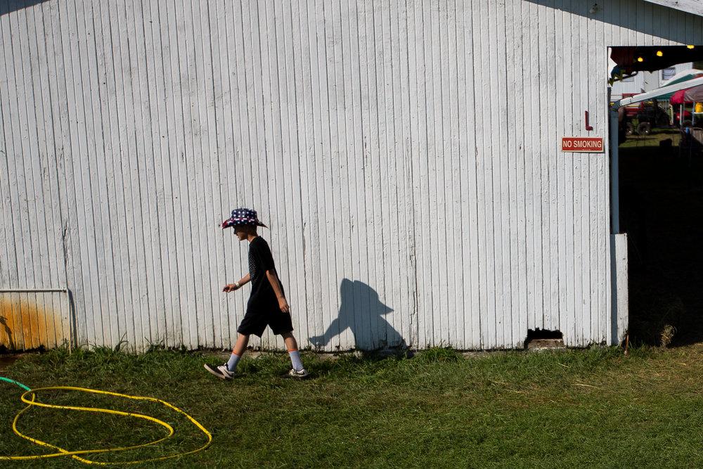 "Trent ""Beanz"" Gurrieri, 11, walks past a barn at the Hookstown Fair in Hookstown on Saturday evening."
