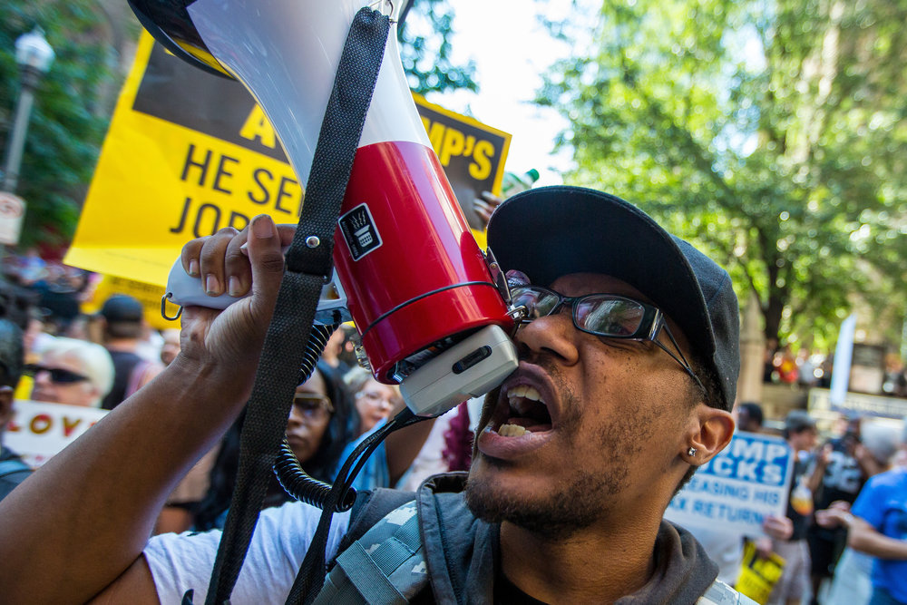 Chris Ellix, of Northside, yells into a megaphone while protesting outside of the Duquesne Club on Sixth Ave. in Pittsburgh on Thursday afternoon. The protest took place after Republican Presidential nominee Donald Trump had lunch at the Duquesne Club following a speech at the Shale Insight conference regarding energy, jobs and trade.