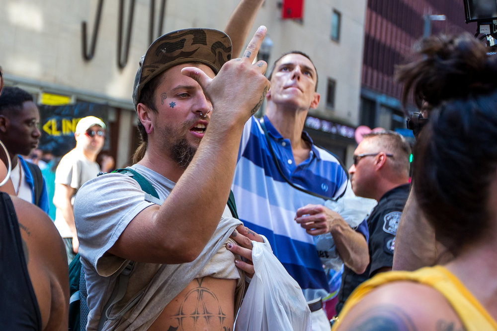 Luke Helbling, of McKees Rocks, flips off Pittsburgh Police during a protest outside of the Duquesne Club on Sixth Ave. in Pittsburgh on Thursday afternoon. The protest took place after Republican Presidential nominee Donald Trump had lunch at the Duquesne Club following a speech at the Shale Insight conference regarding energy, jobs and trade.