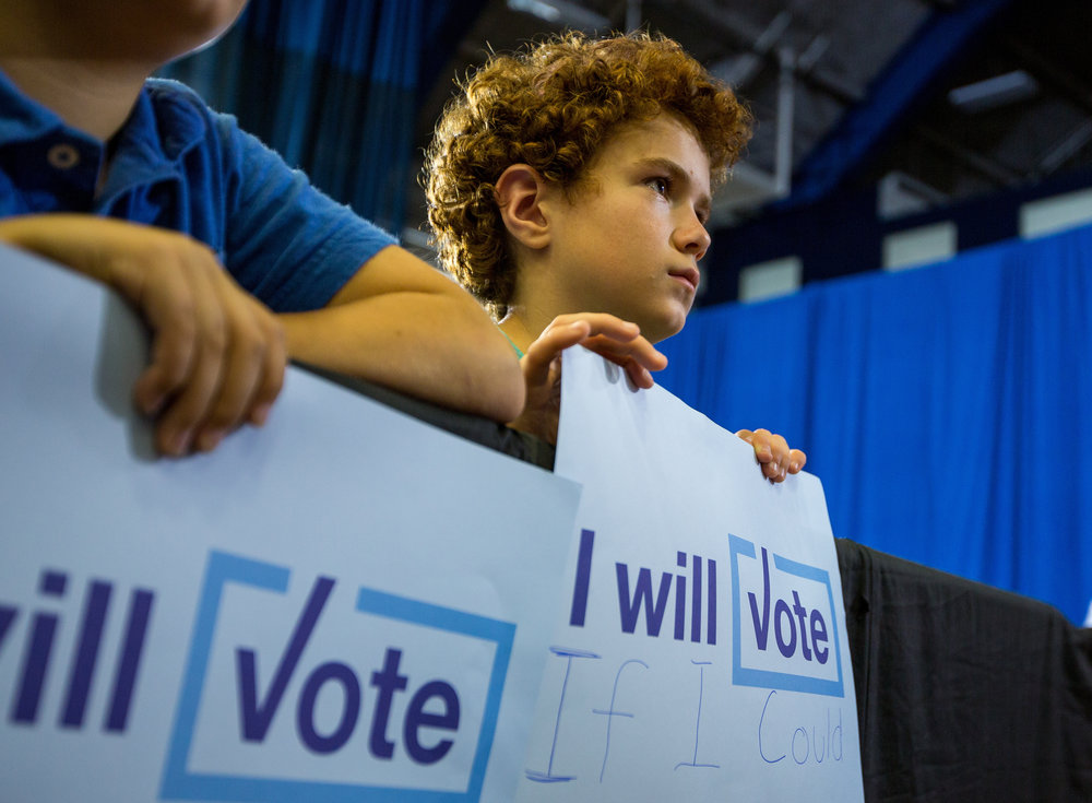 "A young boy holds a sign reading, ""I will vote if I could"" during First Lady Michelle Obamas speech at the Fitzgerald Field House at the University of Pittsburgh on Wednesday afternoon. First Lady Michelle Obama showed her support for Democratic presidential nominee Hillary Clinton and encouraged young people to vote."