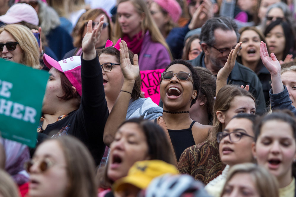 A woman sings at the Diag at the University of Michigan during the Women's March on Saturday, January 21, 2017.  The march was one of several throughout the country and drew over 6,000 people. Matt Weigand | The Ann Arbor News