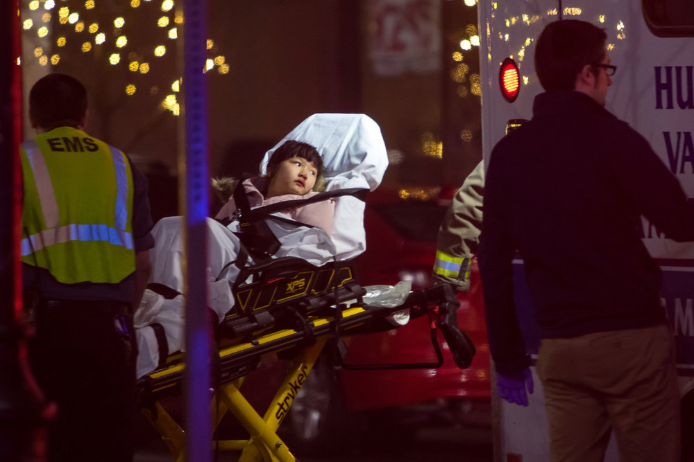 An 8-year-old is carried in a stretcher by EMS after being struck by a USPS truck while crossing Ashley Street at Washington Street with her family. Ann Arbor Police say the 8-year-old suffered minor injuries and the incident remains under investigation. Matt Weigand | The Ann Arbor News