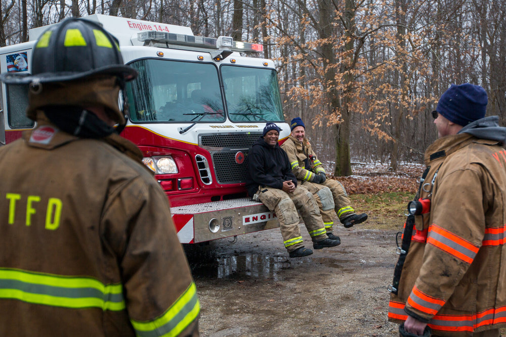 Two members of the Ypsilanti Township Fire Department sit on the front bumper of a fire truck after extinguishing a house fire at 9525 East Bemis Road in Ypsilanti Township on Sunday, January 29, 2017. The fire, which is still under investigation, was called in at about noon. Matt Weigand | The Ann Arbor News
