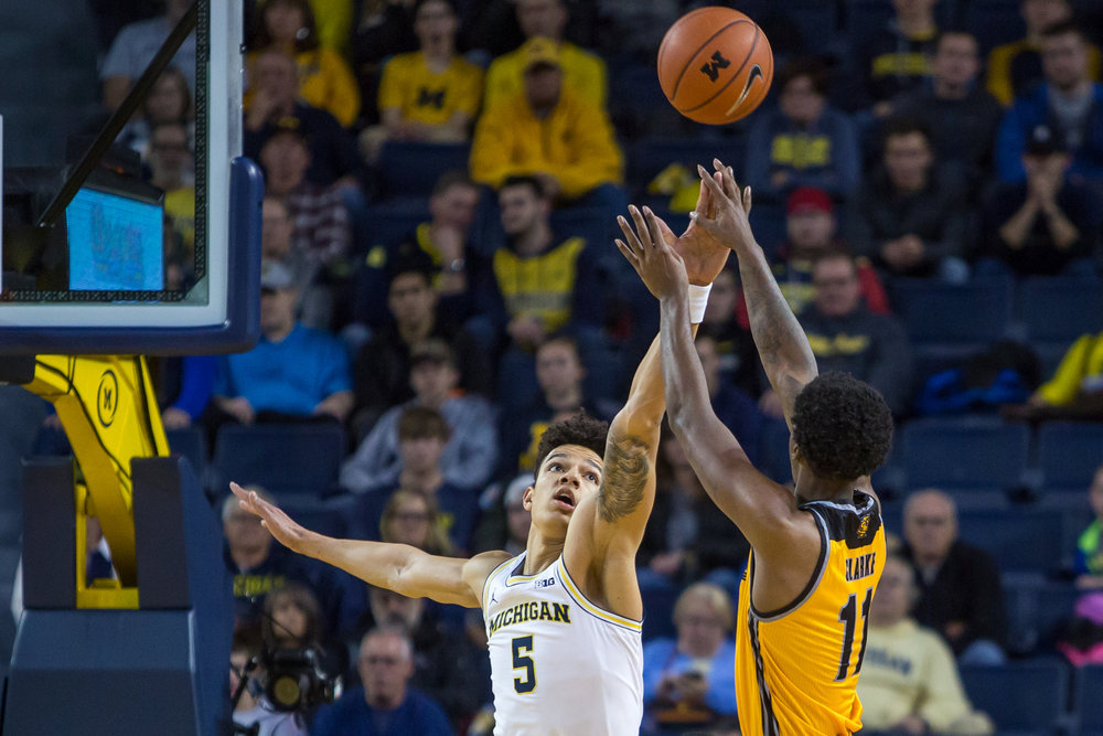 Michigan�s D.J. Wilson (5) attempts to block Kennesaw State's Kyle Clarke (11) during the first half of play against Kennesaw State at the Crisler Center on Saturday, December 3, 2016. Michigan leads Kennesaw State 47-29 at half time. Matt Weigand | The Ann Arbor News