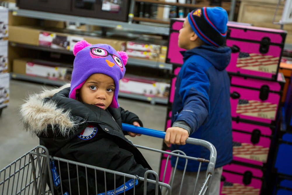 Ta'Nya Phelan, 3, right, sits in  shopping cart while her brother, Juwone Phelan, 12, pushes her while at a shopping trip sponsored by the Warm the Children fund at Walmart in Saline on Friday, December 23, 2016. The Warm the Children fund gathers donations to provide new warm clothing for children in need. Matt Weigand | The Ann Arbor News