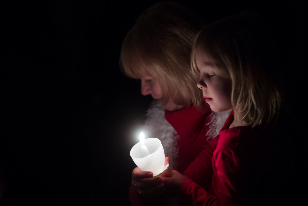 Two churchgoers worship during a candlelit service at Vineyard Church of Ann Arbor worship under candlelight on Saturday, December 24, 2016. Church volunteers delivered 100 dozen donuts from Washtenaw Dairy to people all over the Ann Arbor area who were working on Christmas Eve. Matt Weigand | The Ann Arbor News