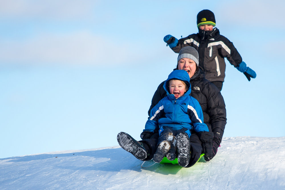 Jessica Anderson, center, sleds down a hill at Burt Park with her son Jude, 4 and help from her other son Liam, 6, on Thursday, February 2, 2017. Matt Weigand | The Ann Arbor News