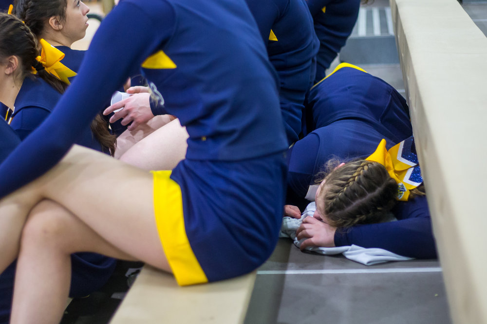 Margie Raupp, Saline High School freshman, lays down after not feeling well after the third round of the 2017 Dexter Competitive Cheer Invitational at Dexter High School on Saturday, February 11, 2017. The Saline team got first place with an overall score of 663. Matt Weigand | The Ann Arbor News