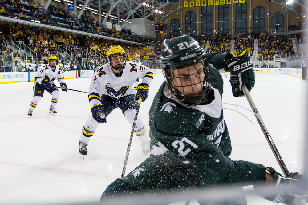 Michigan State's Joe Cox (21) skates after the puck with pressure from Michigan's Luke Martin (2) at Yost Ice Arena on Saturday, February 11, 2017. The Michigan State Spartans beat the University of Michigan Wolverines 4-1. Matt Weigand | The Ann Arbor News