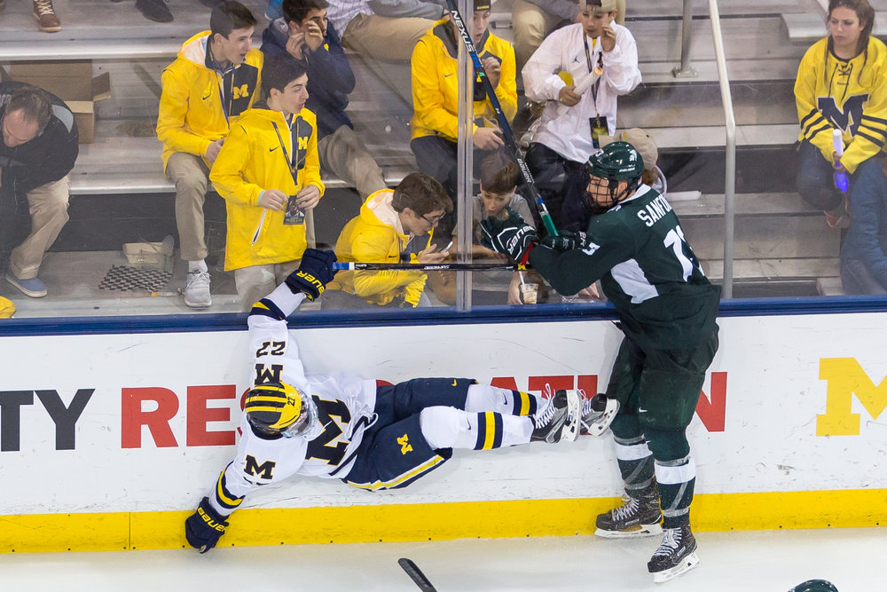 Michigan's Nicholas Boka (27) is thrown into the wall during the matchup against Michigan State at Yost Ice Arena on Saturday, February 11, 2017. The Michigan State Spartans beat the University of Michigan Wolverines 4-1. Matt Weigand | The Ann Arbor News