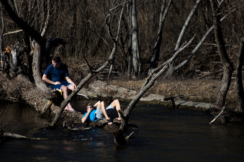 Two individuals sit on a log near the Huron River while at Nichols Arboretum on Saturday, February 18, 2017. According to the National Weather Service, Saturday's high was nearly 58 degrees and locals took advantage of the above average temperatures. Matt Weigand | The Ann Arbor News