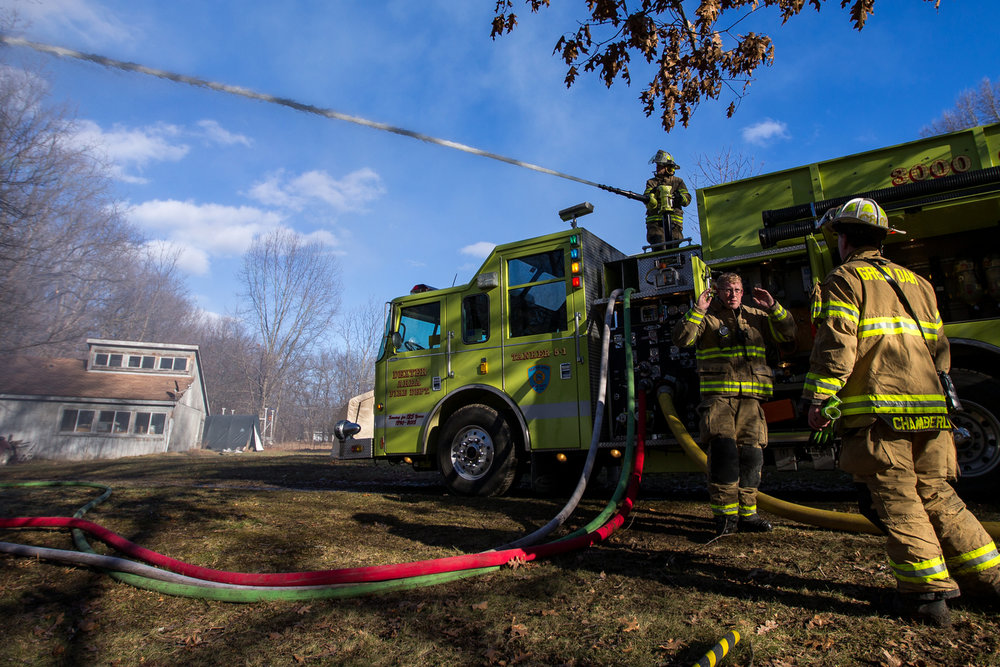 A Dexter area fire fighter sprays water on a structure fire on Scully Road in Webster Township on Friday, March 10, 2017. The fire completely destroyed the home and a nearby field caught on fire. The cause of the fire is still under investigation. Matt Weigand | The Ann Arbor News