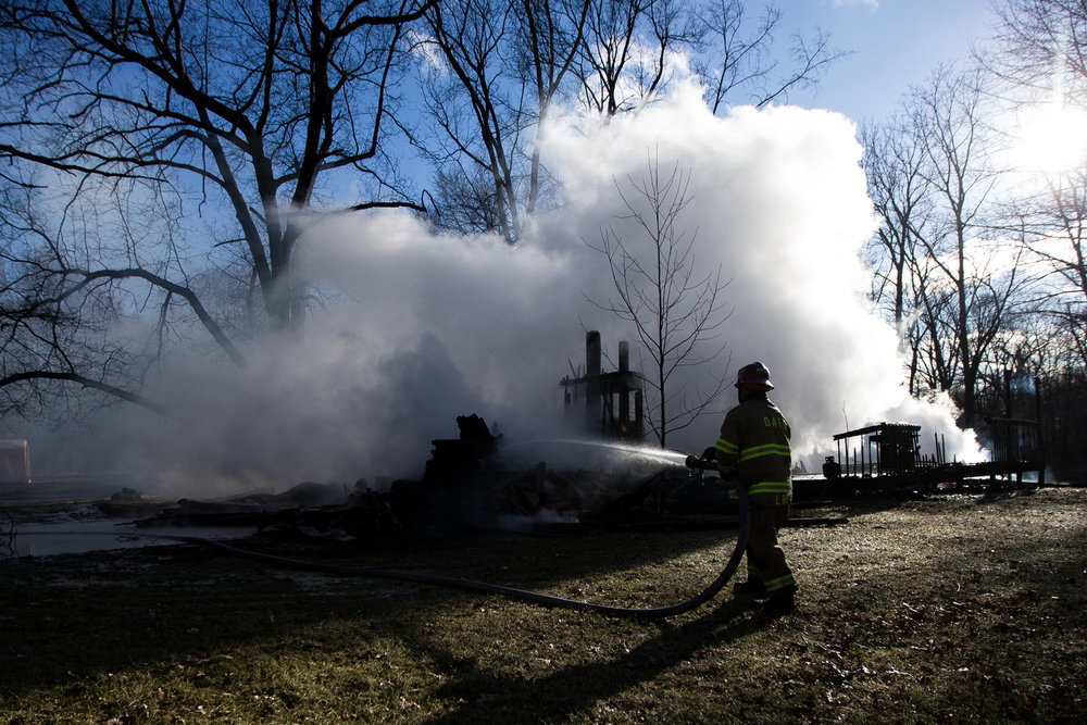 A Dexter area fire fighter sprays water onto a hot spot during a structure fire on Scully Road in Webster Township on Friday, March 10, 2017. The fire completely destroyed the home and a nearby field caught on fire. The cause of the fire is still under investigation. Matt Weigand | The Ann Arbor News