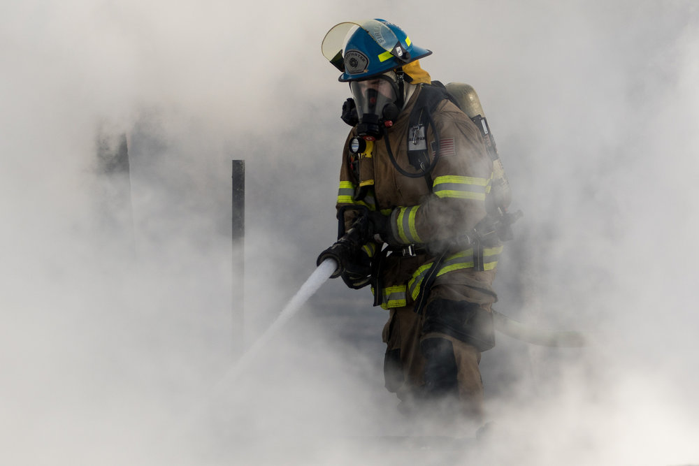 A fire fighter is engulfed in smoke as he works to extinguish a structure fire on Scully Road in Webster Township on Friday, March 10, 2017. The fire completely destroyed the home and a nearby field caught on fire. The cause of the fire is still under investigation.