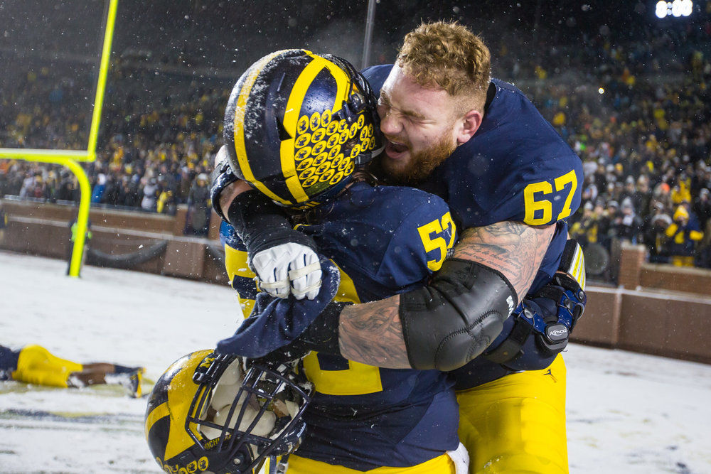 Michigan's offensive lineman Mason Cole (52), left and Michigan's offensive lineman Kyle Kalis (67) celebrate after the completion of the game between the Michigan Wolverines and the Indiana Hoosiers at Michigan Stadium on Saturday, November 19, 2016. Michigan beat Indiana 20-10.