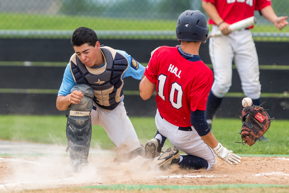 Jarrett Plunkett loses his glove while Jarred Hall slides into home during the first inning on Monday June 29, 2015. The Coeur d'Alene Lumbermen scored three runs during the first inning at Post Falls High School.